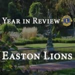 Year in review letter for the Easton Lions header with Queset Gardens image in background.