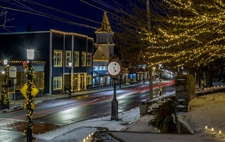 Easton, MA Main Street picture with holiday lights on buildings, posts and trees. Includes clock on street with light snow cover.