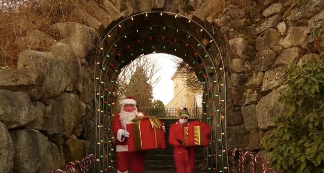 Santa and helper with presents under arch at Rockery in North Easton