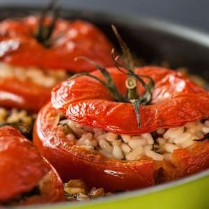 Rice stuffed tomatoes in a pan.