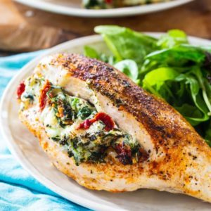 Tuscan stuffed chicken on a plate with lettuce