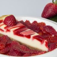 Slice of strawberry cheese cake in a bed of strawberries
